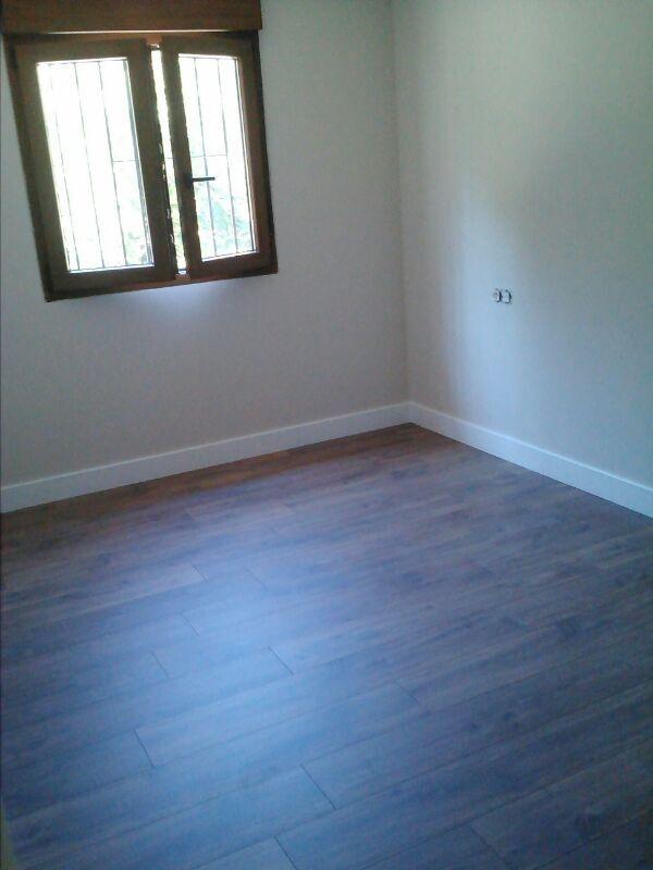 Habitación revestida con suelo laminado marca Quick Step Classic Roble Medianoche